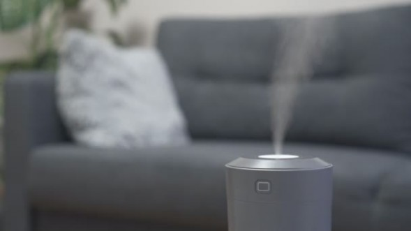 Air humidifier at living room. Man reading book on the background | living room humidifier