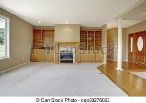 Living room in open floor plan with foyer view and wooden entrance door. | living room entrance