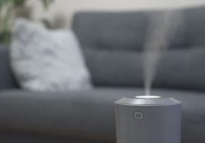 Air humidifier at living room. Man reading book on the background